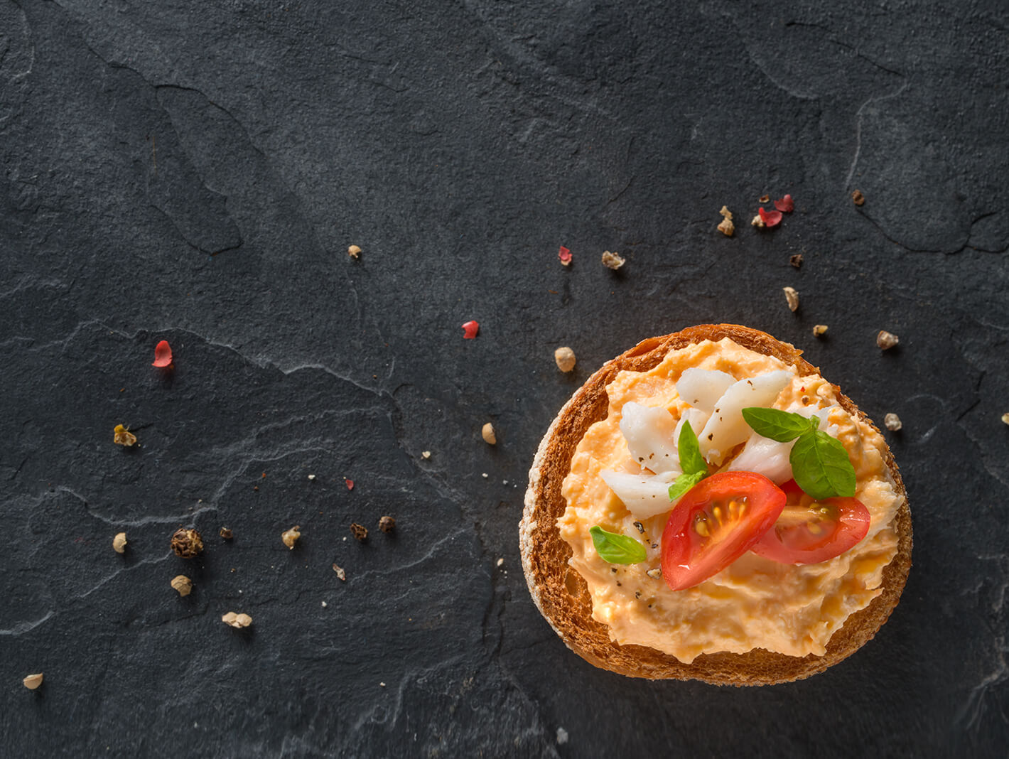 True Blue Seafood Dips, Arial photo of Chunky Crab gourmet dip on a slice of crusty bread with cherry tomatoes and crab pieces, set on a black slate background.