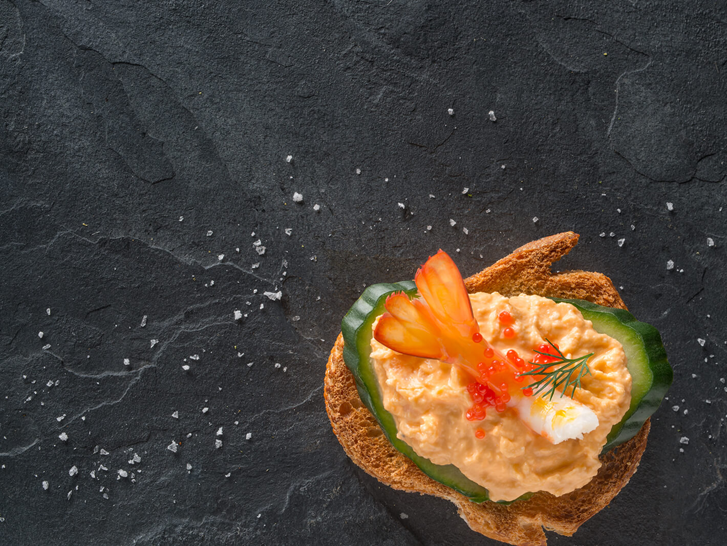 True Blue Seafood Dips, Arial photo of Chunky Prawn gourmet dip on a slice of crusty bread with cucumber, caviar and a prawn tail, set on a black slate background.