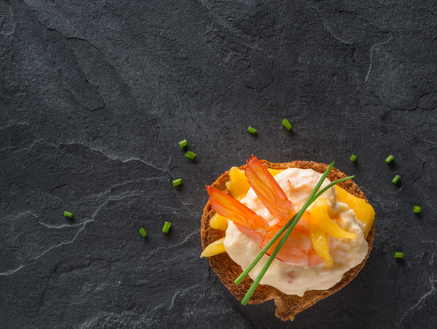 True Blue Seafood Dips, Arial photo of Prawn and Mango gourmet dip on a slice of crusty bread with mango and prawn tail, set on a black slate background.