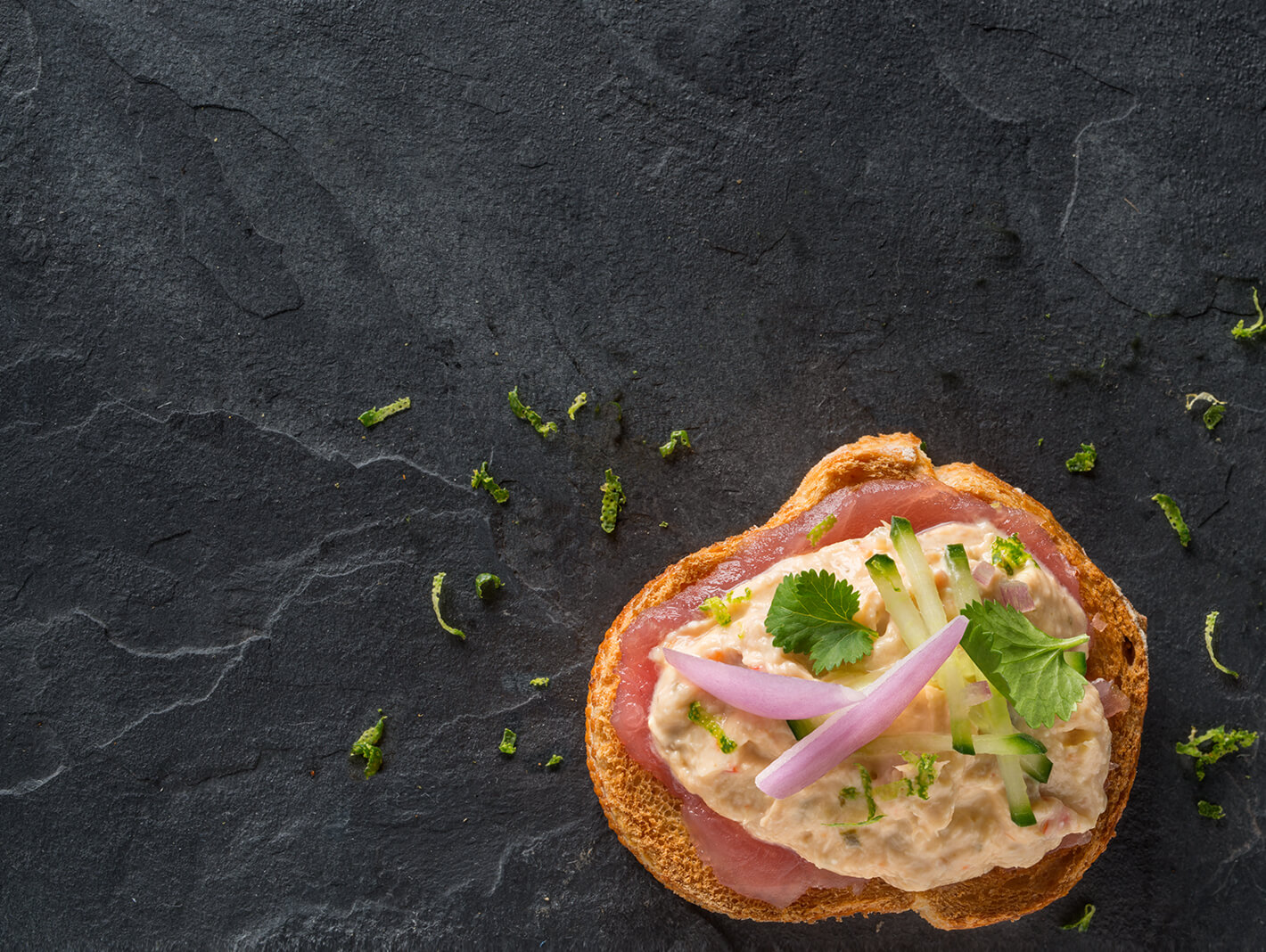 True Blue Seafood Dips, Arial photo of Thai Tuna gourmet dip on a slice of crusty bread with a slice of Tuna, chopped cucumber and onion slices, set on a black slate background.